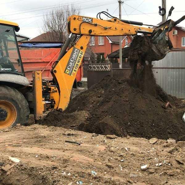 Экскаватор роет яму